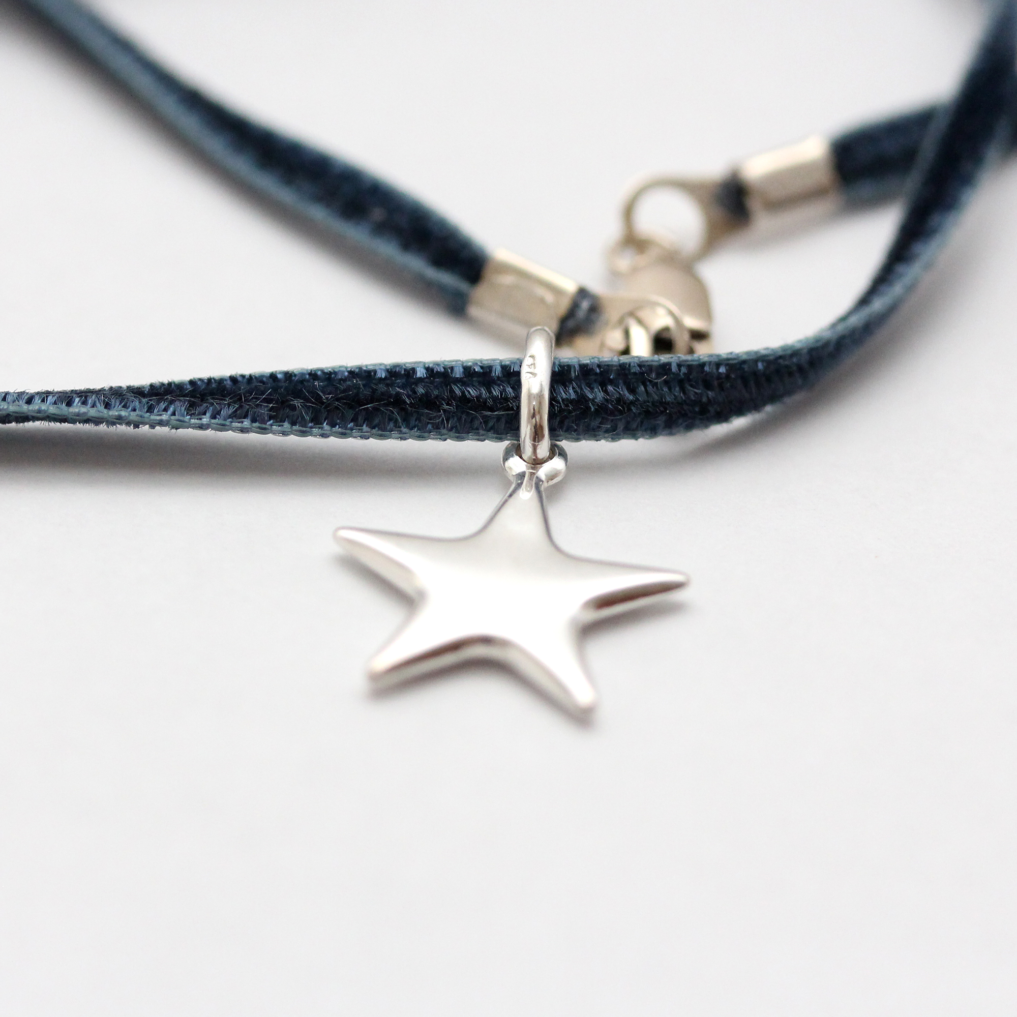 Sterling silver star on a navy blue double sided velvet necklace.